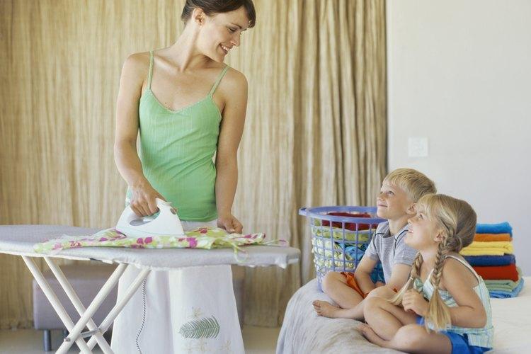 Madre planchando la ropa al lado de los niños.