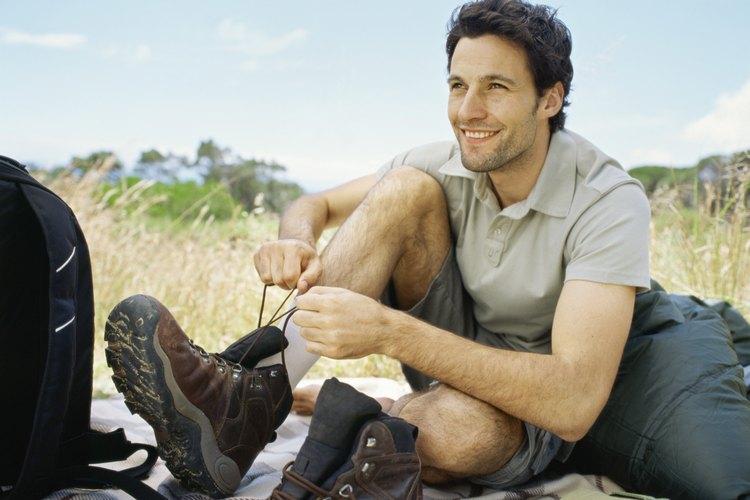 Hombre atando sus botas de senderismo ecológicas