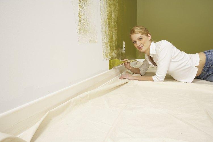 Una mujer pintando la pared, de color blanco.