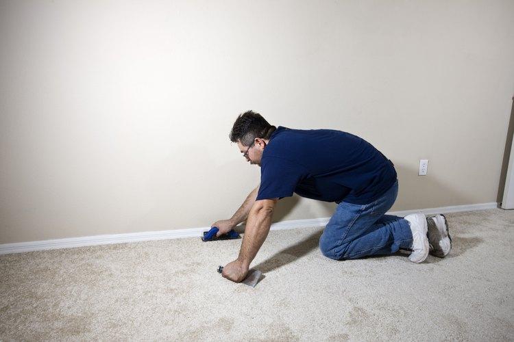 Instalador profesional retirando la alfombra vieja.