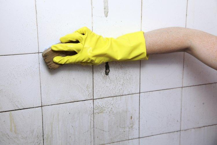 Frota las manchas de aceite de la pared con la esponja.