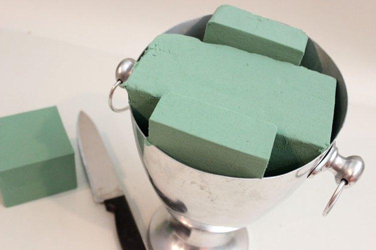 Corta la espuma floral para que quepa dentro del recipiente.