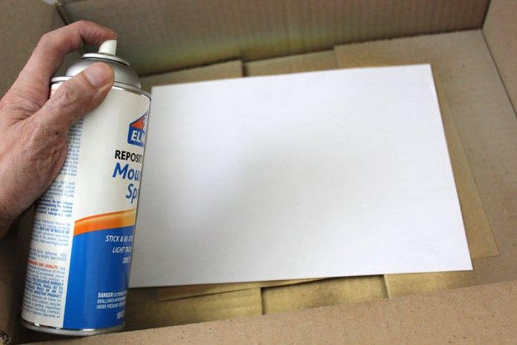 Rocía el adhesivo sobre la parte posterior del papel.