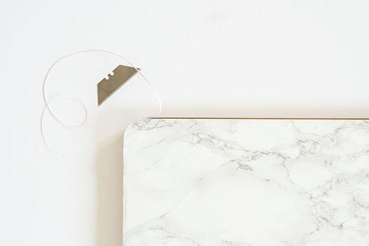 El papel adhesivo de imitación de mármol se puede cortar de un tamaño que se ajuste a cualquier superficie.