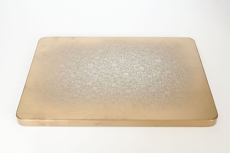 La pintura dorada le añade un brillo metálico a los bordes de la mesa.