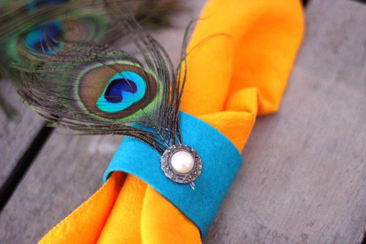 Crea un anillo para servilletas con una pluma de pavo real para que haga juego.