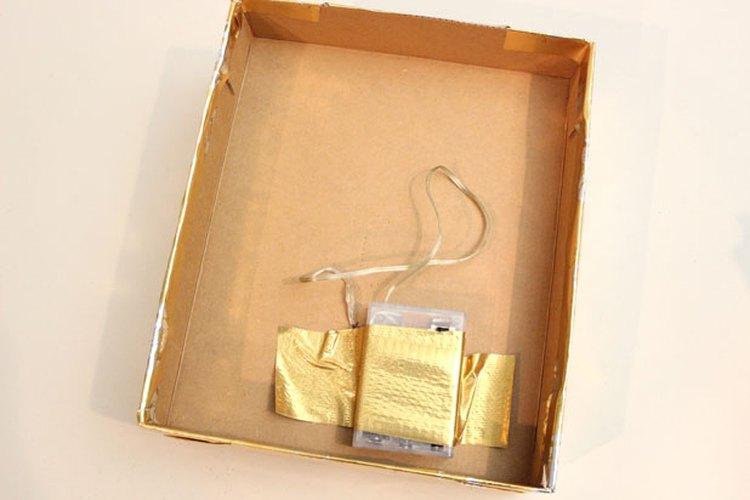 Pega la batería a la parte interior de la tapa con cinta de embalar.