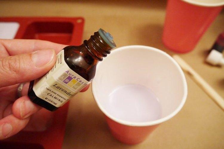 Transfiere el jabón derretido a otro recipiente resistente al calor, como un vaso de papel para café, para añadirle el colorante o la fragancia.