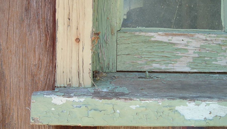 The cracked and peeling paint surface of an outside window sill.