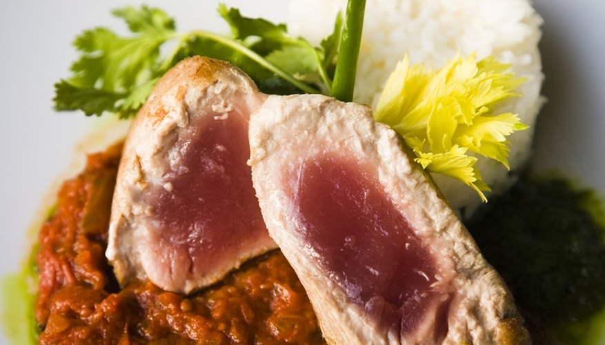Bake tuna steaks in the oven until they begin to flake.