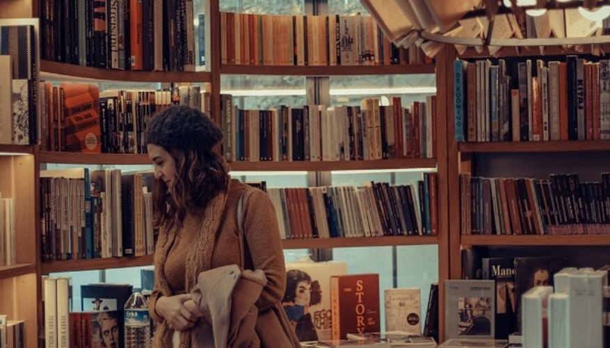 Woman in brown coat reading book in library.jpg