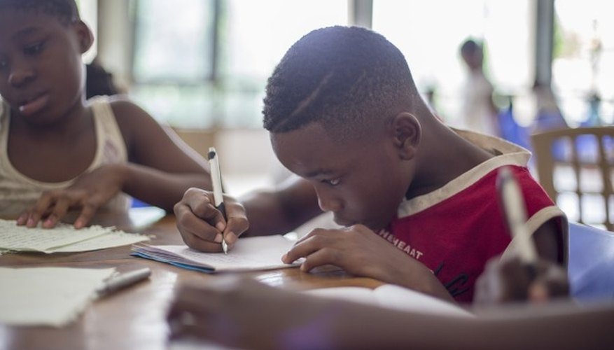 Boy writing on printer paper near girl.jpg