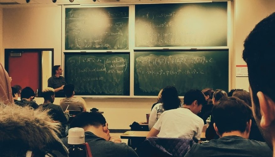 Student sitting on chairs in front of chalkboard.jpg
