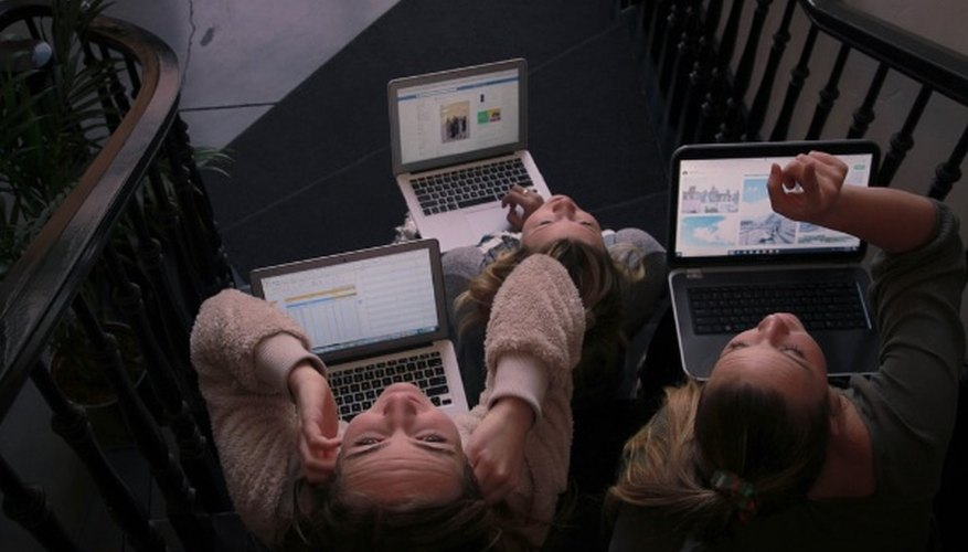 Three person using laptops while sitting on ladder.jpg