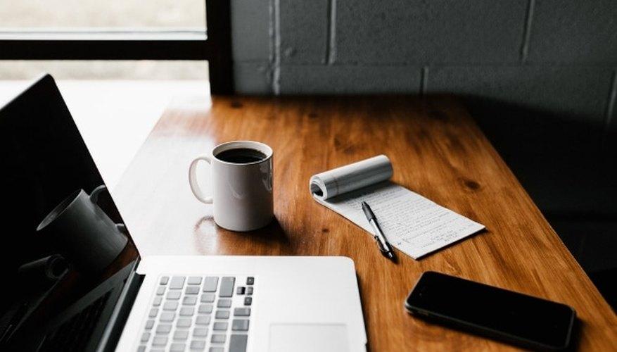 Macbook pro, white ceramic mug,and black smartphone on table.jpg