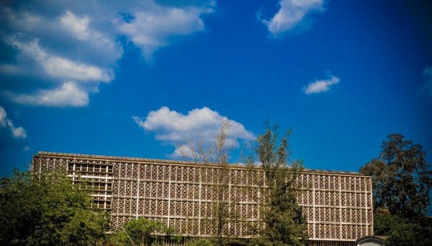 White concrete building near green trees under blue sky during daytime.jpg