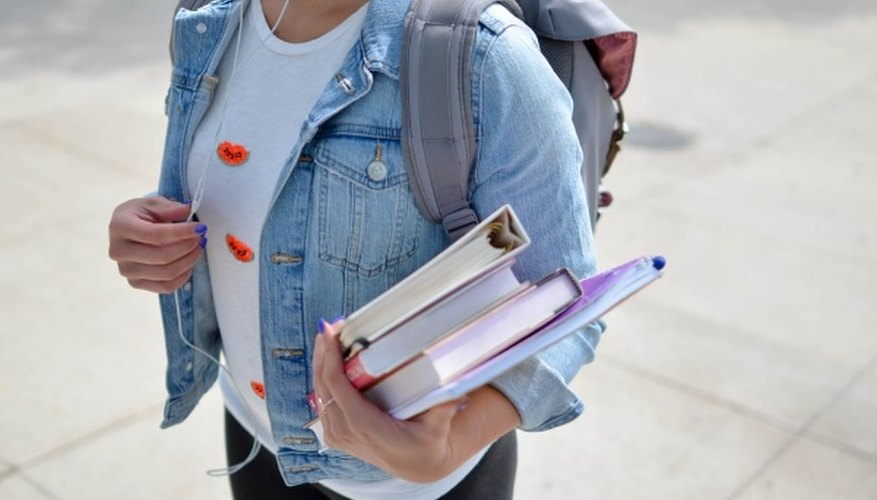 Woman wearing blue denim jacket holding book.jpg