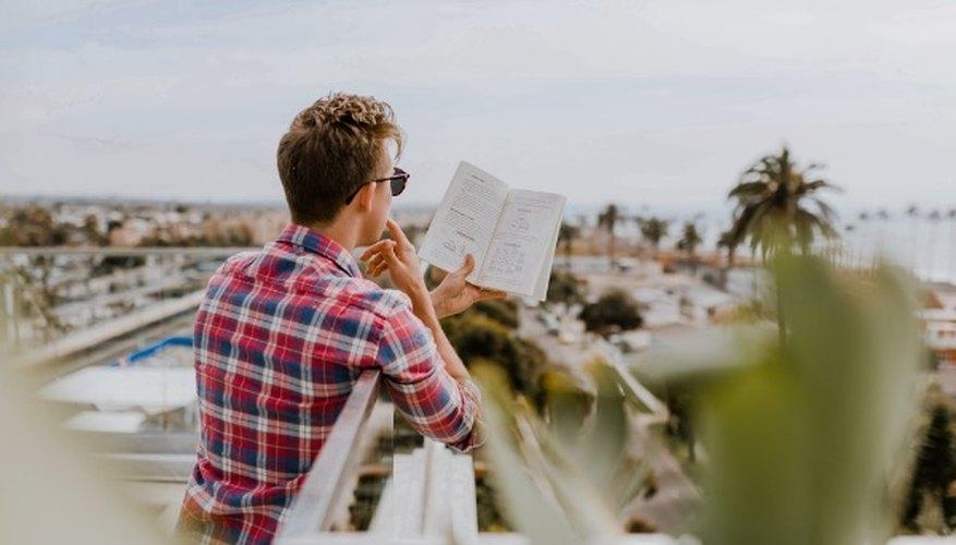 Man reading book on balcony during daytim.jpg