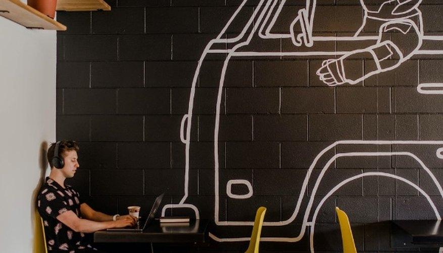 Man wearing headphone using laptop while sitting beside table inside cafe.jpg