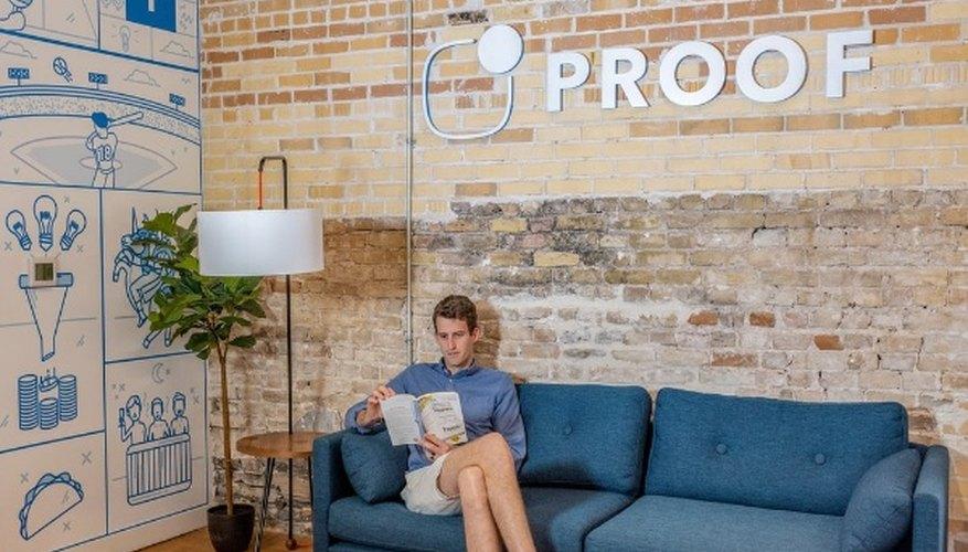 Man sitting on blue sofa while reading book.jpg