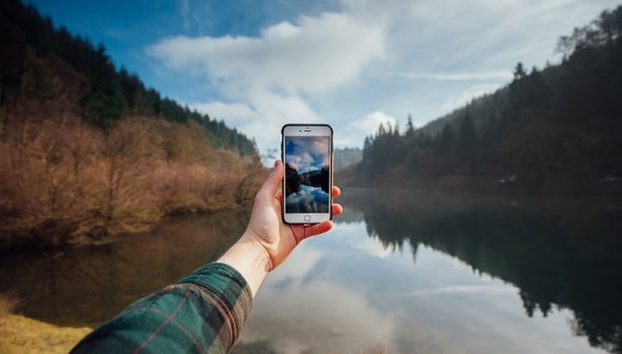 Person holding iphone while taking picture of mountains and body of water during daytime.jpg