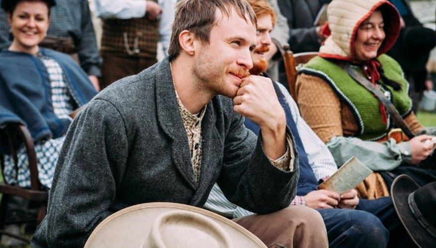Man wearing black coat sitting beside man in blue vest during daytime.jpg