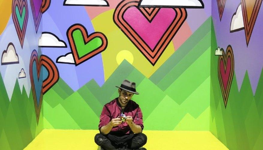 Man sitting on multicolored 3d wallpaper room.jpg