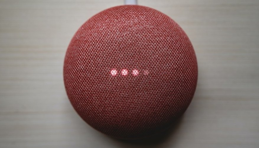 Red round portable speaker on brown wooden table.jpg