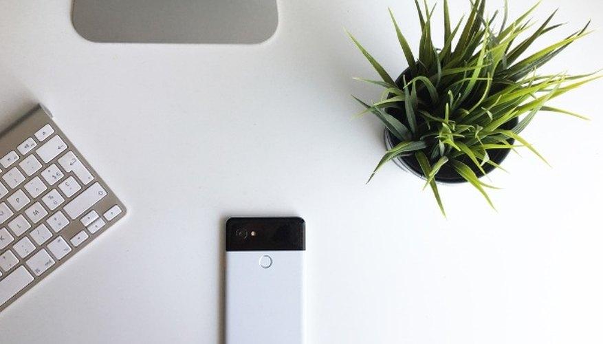 White google pixel phone beside keyboard.jpg