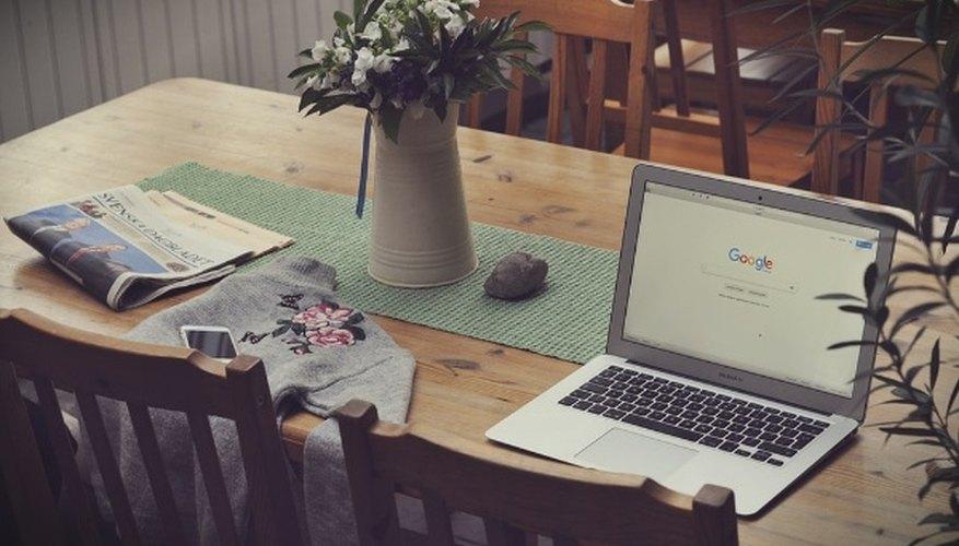 Laptop on top of table beside vase of flowers.jpg