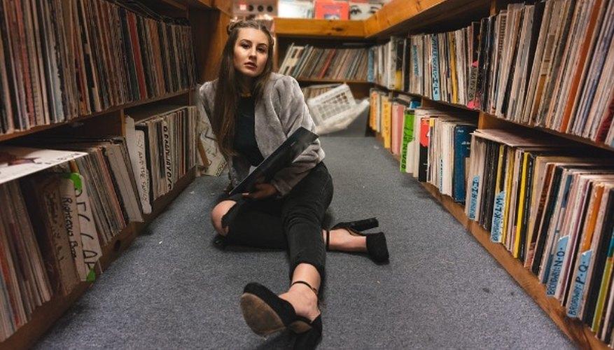 Woman sitting on floor between bookshelves.jpg