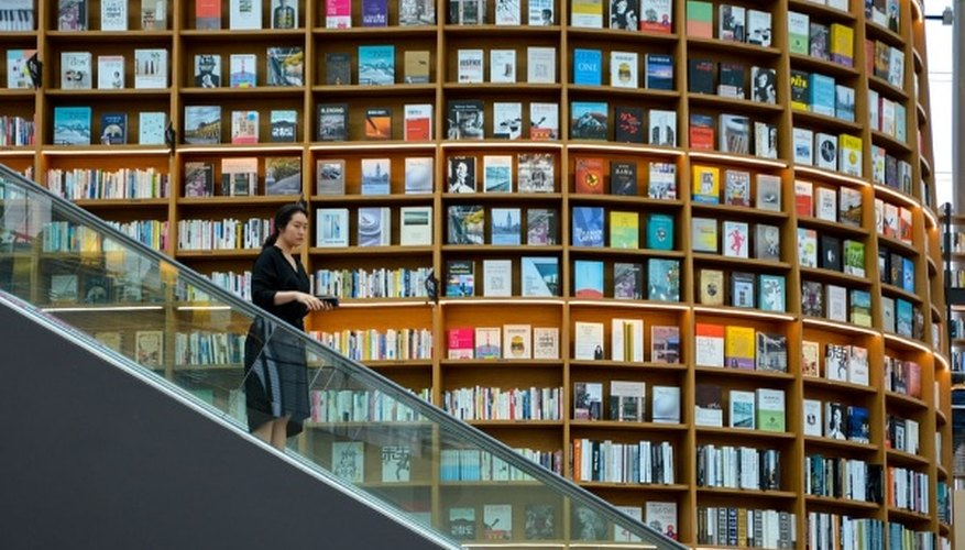 Woman standing on escalator near brown wooden book shelves.jpg