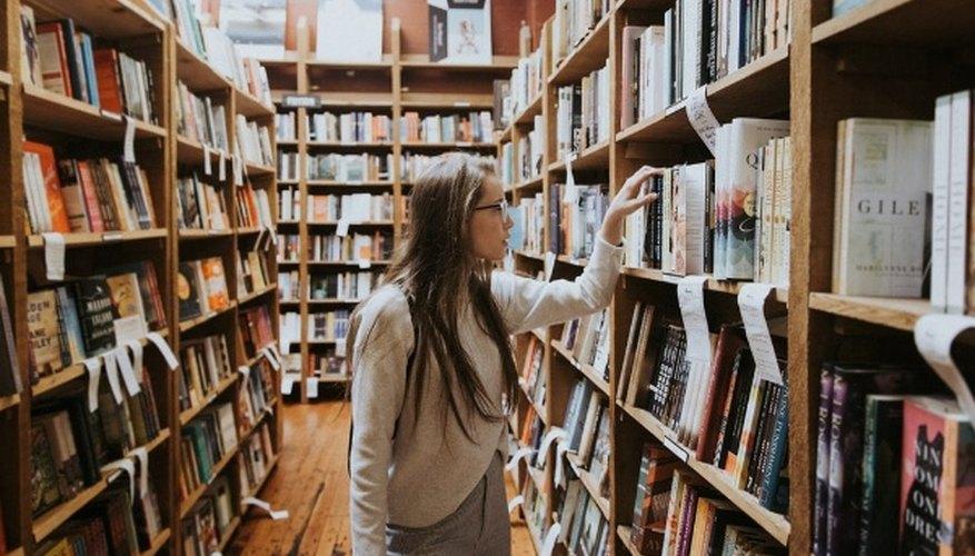 Woman holding book on bookshelves.jpg