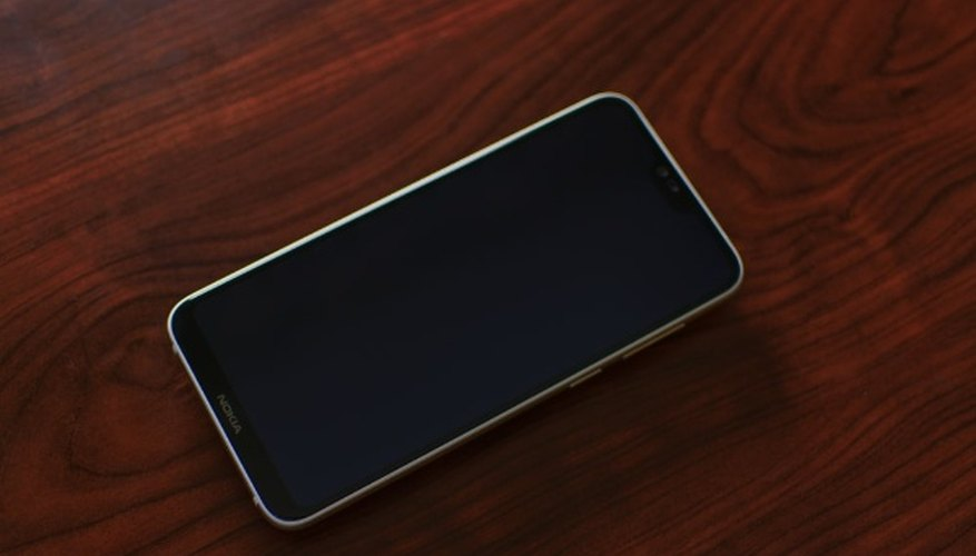 Black smartphone on red stained wood panel.jpg