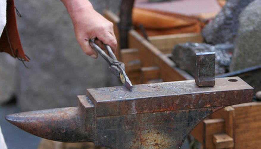 The medieval blacksmith hammered metal on an anvil.