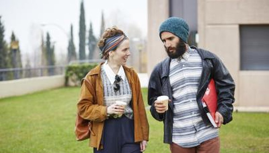 Hip, fashion students walking through campus with coffee and binders