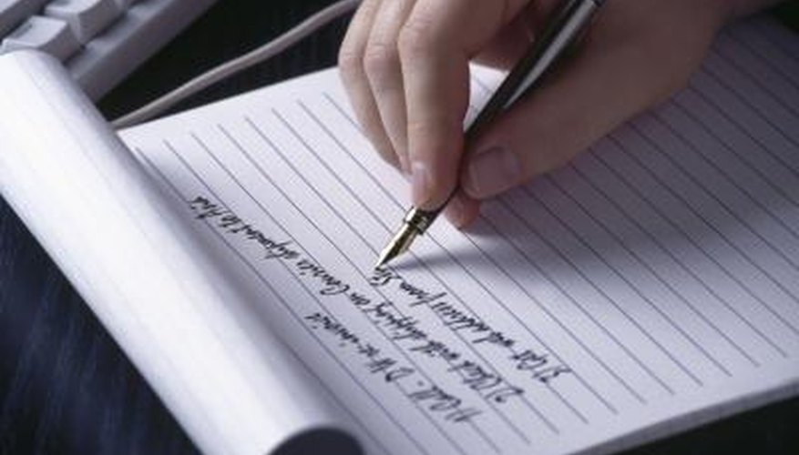 Hand writing a list on a notepad.