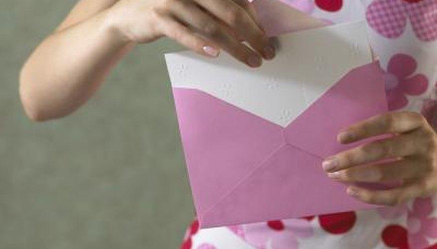 Woman taking card out of handwritten envelope.