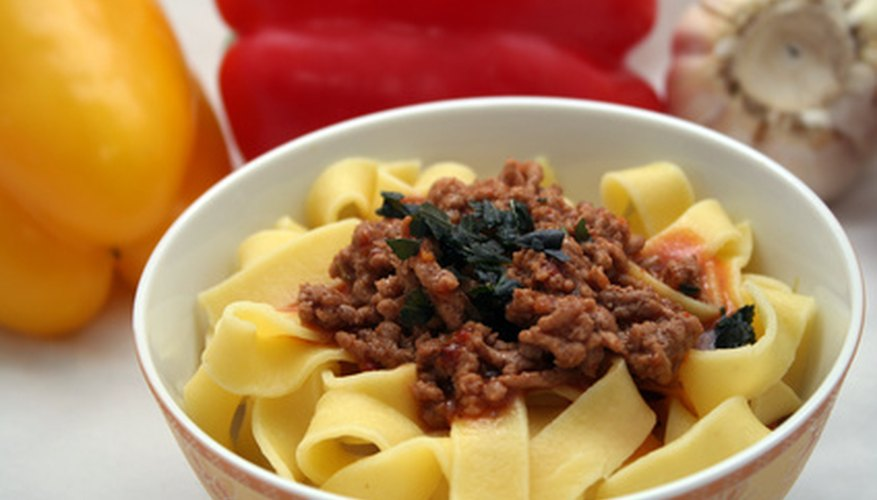 Pasta topped with fresh vegetables and ground beef: a healthy, satisfying meal.