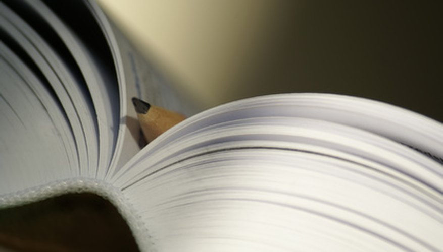 Straighten your curled paperback book by using two hardcover books to support it.