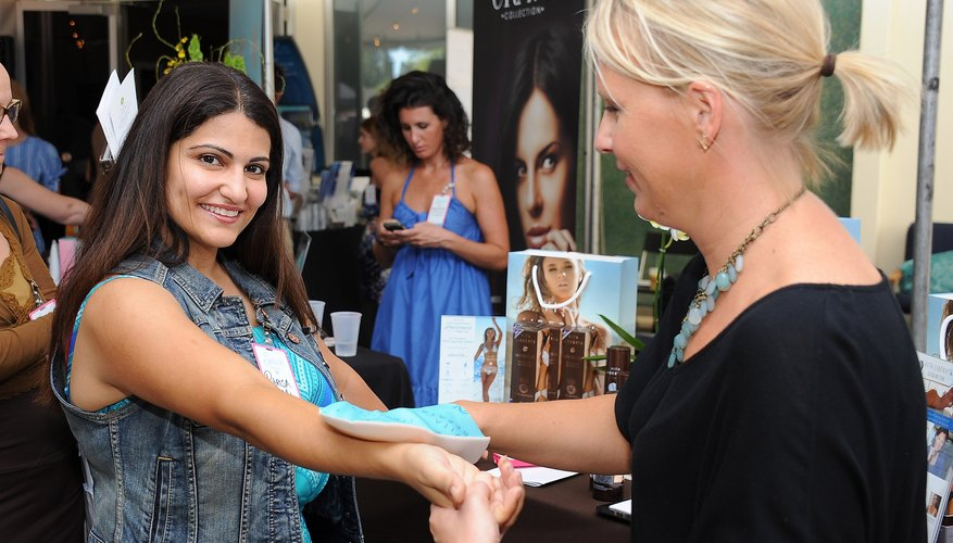 A cosmetologist applying a hand treatment to a woman at a salon event.