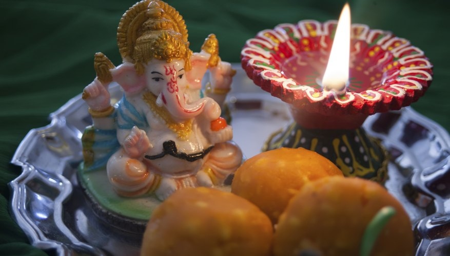 A Ganesh statue, prayer candle, and sweet treats on a plate.