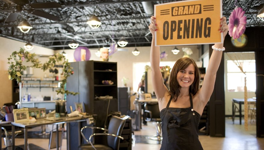 An excited salon owner holds up an open sign.