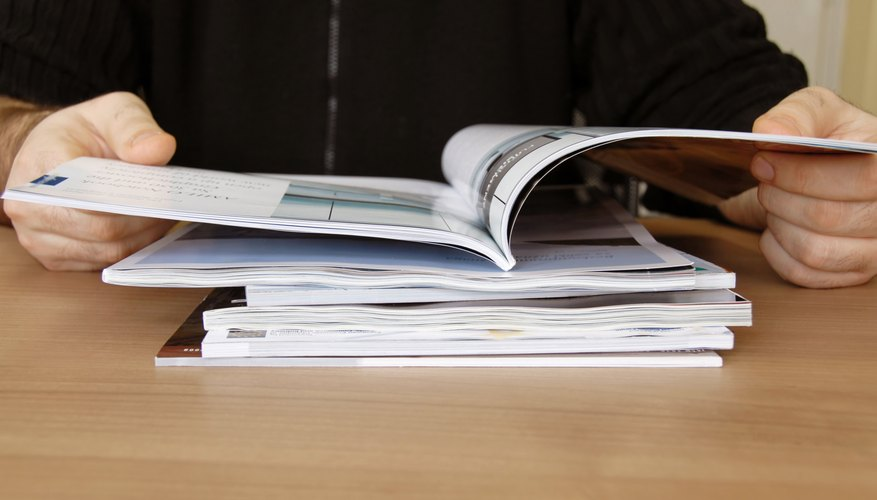 Close-up of man reading research journals.