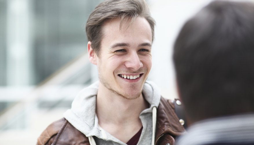 Man smiling while having conversation with friend