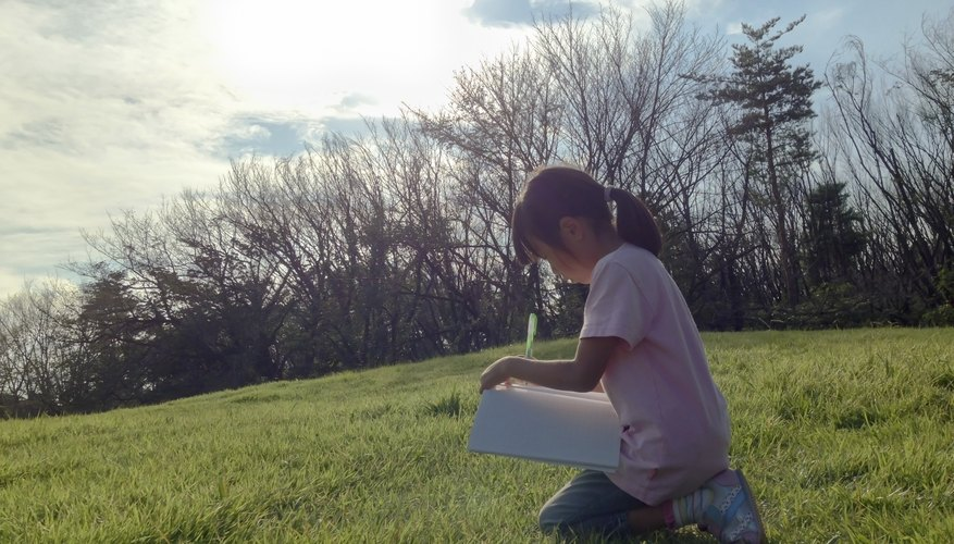 Young girl writing in journal while kneeling on grass.