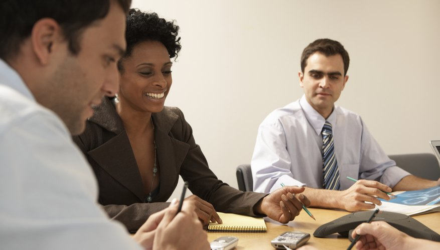 A group of professionals conducting a business meeting at a conference table.