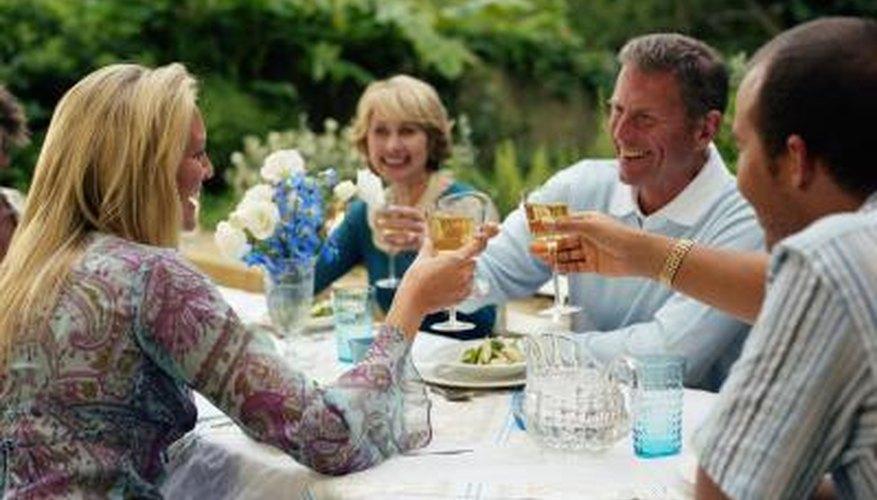 Un grupo de personas hacen un brindis en una mesa exterior.