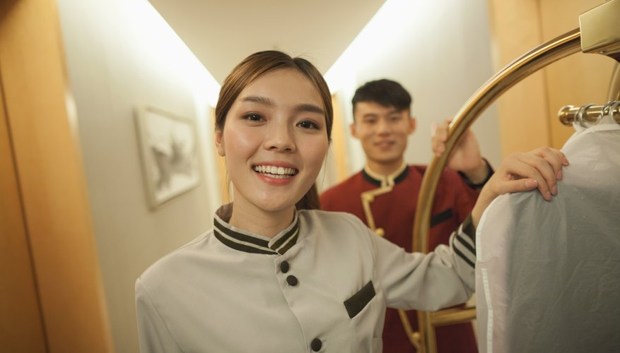 Two young employees smiling in a hotel corridor.
