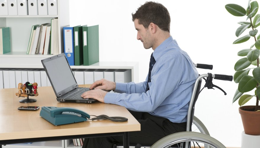 A disabled man sits at his desk in a wheelchair.